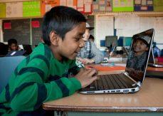 Namir Abdullah enjoys e-learning on the school's new laptops at Mason Road Public School