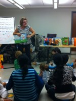 Parents and their children listen to Marianna during story time.