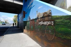The east wall of the mural depicts the Bell Estate home and a wagon.