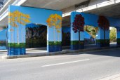 The portion of the mural on the central columns depict birch and oak trees, which represent Ward 35 and Ward 36. Behind the columns, an outline of The Bluffs is visible on the west wall of the Warden underpass.