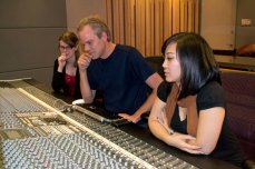 Amanda Rabey (left) seated with Mike Smith and Jen Fabico at the control panel in Phase One's recording studio.