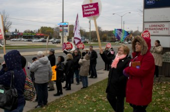 Fighting the cold, protesters get the attention of drivers as they leave the strip mall where MPP Lorenzo Berardinetti's constituency office is located. This was one of five stops to local MPP offices made by the Scarborough Health Coalition's Nov. 9 rolling rally.