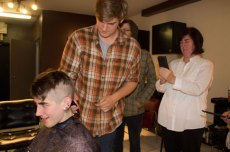 Newell's brother, Marrick, takes a turn shaving his sister's head while her mother, Melissa, takes a video.