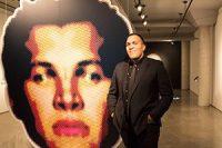 "Mario Schambon stands beside his work ""Cara Falsa"", a mirror image of his face."