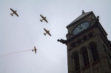 Harvard Trainers fly in a missing man formation over Remembrance Day services at Toronto's Old City Hall