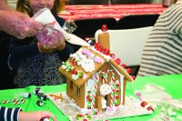 David Lewis adds piping to the gingerbread house his wife and grandchildren designed at Habitat for Humanity's 11th annual Gingerbread Build.