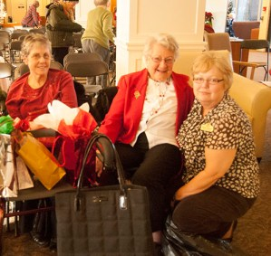 Karen Sansom, director of recreation at CedarBrook Lodge Retirement Residence, smiles with a member of the choir and a resident at the retirement home.