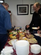 People at the art exhibition enjoy light snacks and refreshments.