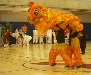 Orange dragon dancers display enthusiasm and excitement.