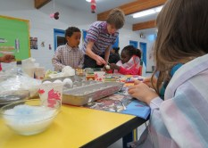 Gregg showing the children how to dye their eggs.