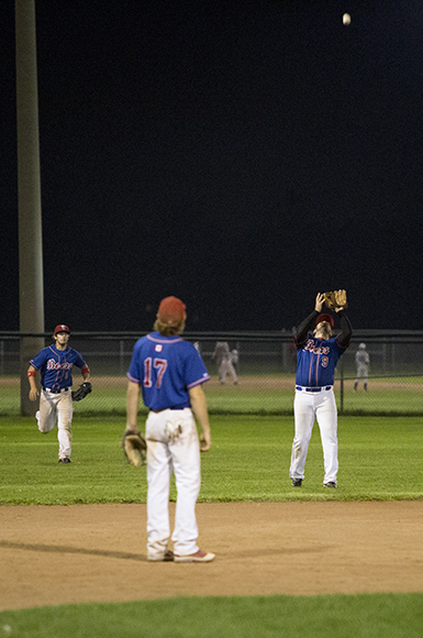 Josh Grassick, centre, looks on as Kyle Nicoletta, left, catches a fly ball off the bat of Mike Guilfoyle to end the third inning.