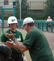 Head Coach Ken Eriksen (right) gives some hitting tips to Meredith Bissette (left) during batting practice