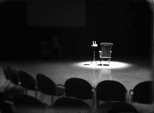 A audience member is chosen to be a medium in the seance.