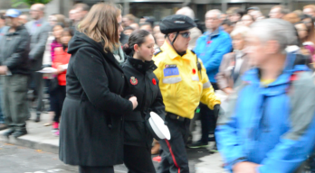 A woman in mourning is helped out of the crowd during the reading of In Flanders Fields.