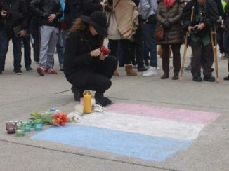 A woman lights a candle to commemorate the fallen.
