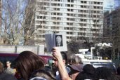 A supporter silently holds a black and white photo of Rob Ford above his head.