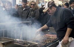 Employees from Kalyvia set up an outdoor barbecue and grill station, serving barbecue pork.