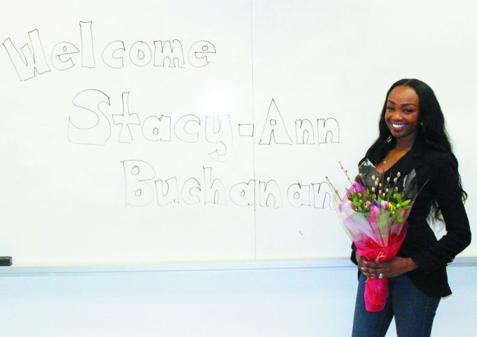 Stacy-Ann Buchanan poses with flowers given to her by Centennial College students.