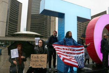 Yvon Wang, a history professor from University of Toronto, holding an American flag at the protest.