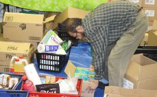 Thorncliffe food bank coordinator Zeeshan Modi opening a box of donated food to hand out to food bank visitors.