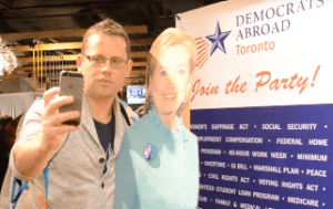 A man poses with a cardboard cutout of Hillary Clinton at a viewing party held by Democrats Abroad in Toronto.