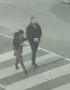 A man and woman crossing the street
