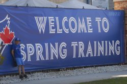 """A young fan poses beside the """"Welcome to Spring Training"""" sign at Florida Auto Exchange Stadium. (Jonathan Cheng photo)"""
