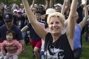 Premier Kathleen Wynne, participates in stretching before the run.