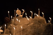 Individuals place candles on snow bank at the LGBTQ community vigil organized by The 519.