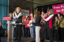 Wynne speaking on stage, in front of her applauding supporters.