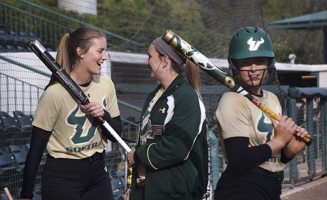 Female softball players laughing