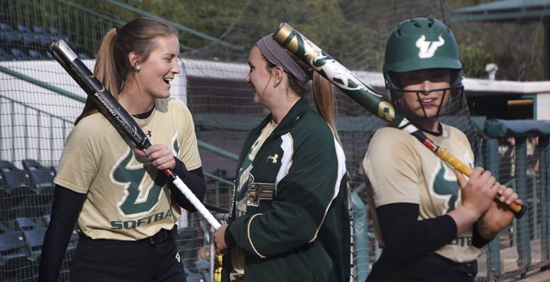 Female softball players laughing