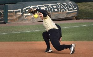 softball player catches a ball between second and third base