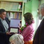 El Concejal de Educación entrega a Mª Carmen una placa con el reconocimiento del Ayuntamiento de Torrelodones a su labor