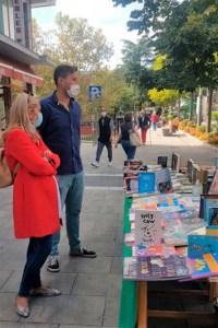 Alcaldesa de Collado Villalb y el edil de Desarrollo Local, mirando un puesto del Rastro del Libro en la calle Real