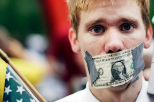 A demonstrator from the Occupy Wall Street campaign stands with a dollar taped over his mouth in Zucotti Park near the financial district of New York