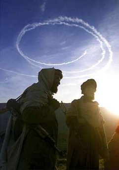 Afghan anti-Taliban fighters are silhouetted below the contrails left by U.S. jets on a bombing sortie in the Tora Bora mountains, in this file picture taken December 14, 2001.
