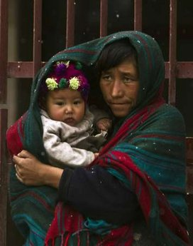 An Afghan woman holds her child as it snows in Kabul March 2, 2011.