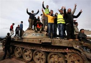 Anti-government protesters make victory signs as they stand on an army tank near a square where people protest in Benghazi city