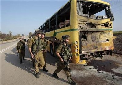 Israeli soldiers walk near a bus that was damaged by an anti-tank missile fired from the Gaza Strip into southern Israel