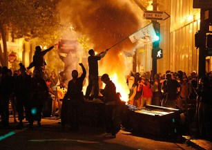 A demonstrator waves a banner as rubbish burns at the Occupy Oakland demonstration. Nov. 3 2011