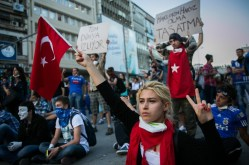 A young woman holds a Turkish flag while blocking a main road in the centre of Ankara. Many of the protesters are young people who are more in-tune with Western values