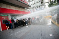 Police spray protesters with a water cannon as demonstrators take cover near a bank. Turkey is not a second-class democracy, Turkish Foreign Minister Ahmet Davutoglu told US Secretary