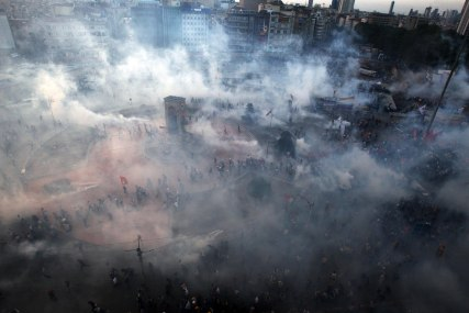 Protesters run to avoid the tear gas during clashes at the Taksim Square in Istanbul Tuesday, June 11, 2013. AP Thanassis Stavrakis
