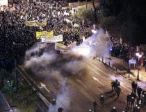 Protestors carrying banners stand amidst tear gas fired by riot police during demonstrations outside the Greek parliament building on Syntagma Square in Athens, Greece, Feb. 12, 2012