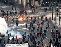 Riot police stand amongst tear gas and petrol bombs as they clash with protestors outside the Greek parliament in Athens, Greece, Feb. 12, 2012.