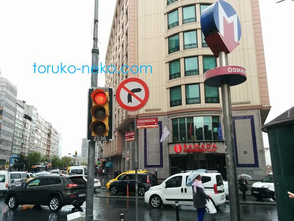 オスマンベイ駅の看板の向こうに ラマダホテルが見えている写真 画像