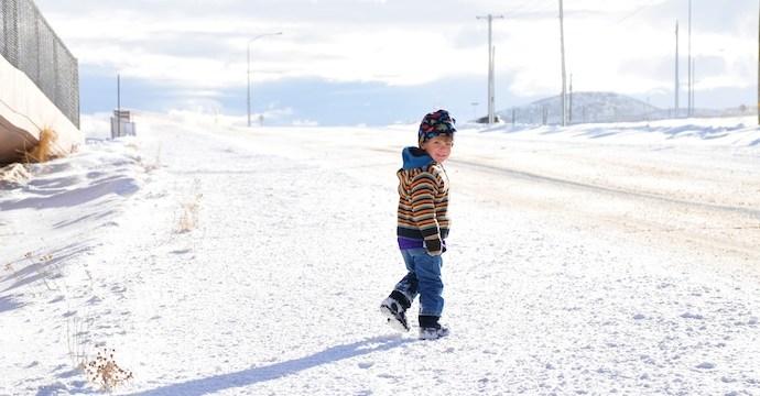Tory walks on a snow sidewalk