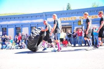 Strongmen lifting heavy things down the street.