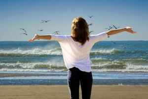 海辺で気を受け取る女性